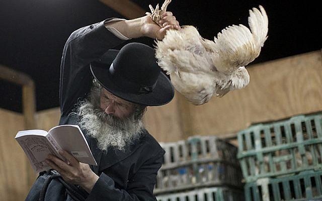 Illustrative image of an ultra-Orthodox Jewish man in a religious neighborhood in Ashdod performing 'kapparot' ritual before Yom Kippur. (Dima Vazinovich/Flash90)