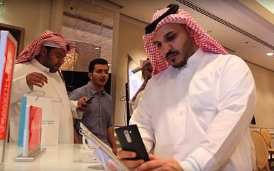 Saudi men trying out smartphones at a conference. (YouTube screenshot)