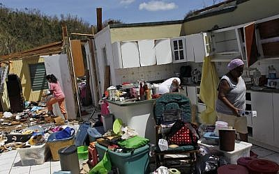 Family members collect belongings after hurricane force winds destroyed their house in Toa Baja, west of San Juan, Puerto Rico, on September 24, 2017 following the passage of Hurricane Maria. (AFP PHOTO / Ricardo ARDUENGO)