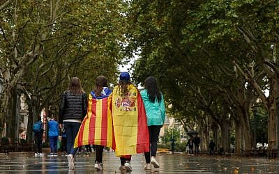 Girls stroll through the center of Figueras with the Spanish and a pro-independence 'Estelada' Catalan flag on September 30, 2017 in Figueras (AFP PHOTO / CESAR MANSO)