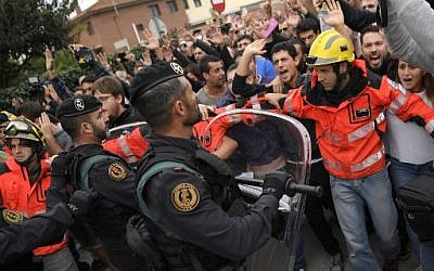 Firemen try to hold a group of people outside a polling station in San Julia de Ramis, on October 1, 2017, on the day of a referendum on independence for Catalonia banned by Madrid. (AFP PHOTO / LLUIS GENE)