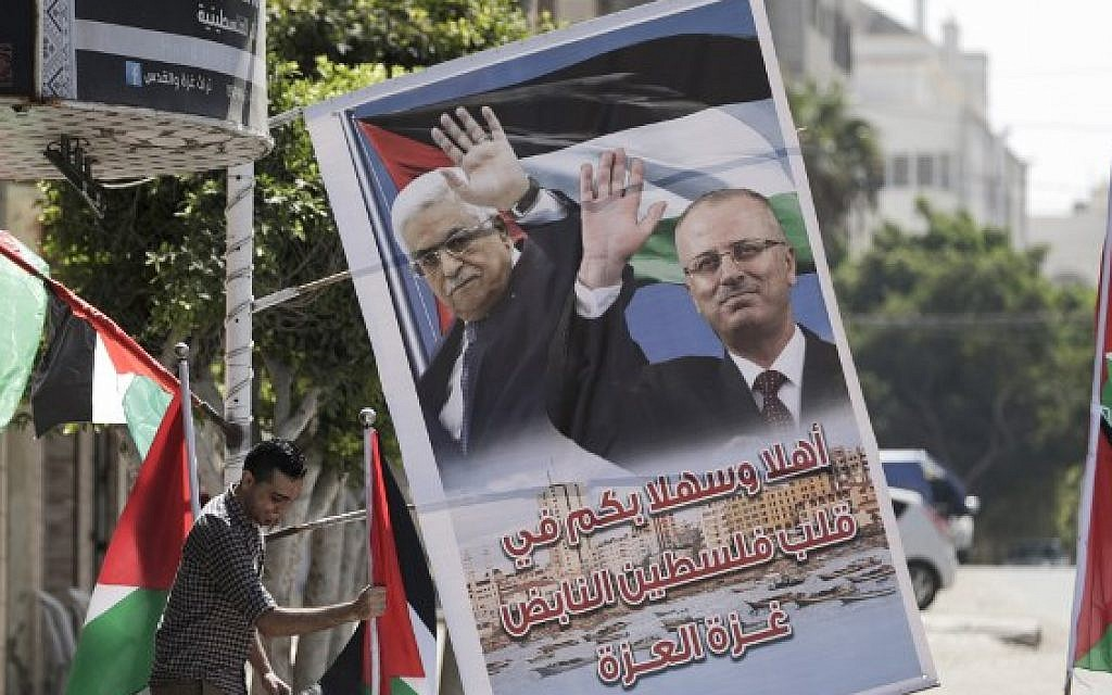 A Palestinian shop owner displays national flags and a poster bearing the portraits of Palestinian Authority prime minister Rami Hamdallah and leader Mahmoud Abbas on October 1, 2017, in Gaza city. (AFP Photo/Mahmud Hams)