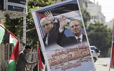 A Palestinian shop owner displays national flags and a poster bearing the portraits Palestinian prime minister Rami Hamdallah and Palestinian leader Mahmoud Abbas on October 1, 2017, in Gaza city. (AFP PHOTO/MAHMUD HAMS)