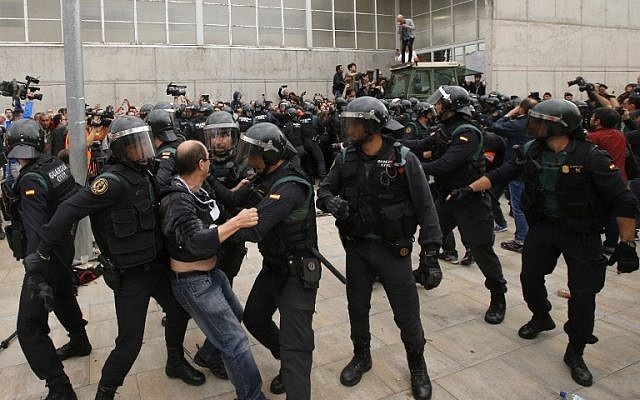 A man clashes with Spanish Guardia Civil guards outside a polling station in Sant Julia de Ramis, where the Catalan president was supposed to vote, on October 1, 2017, the day of a referendum on independence for Catalonia banned by Madrid. (AFP PHOTO / Raymond ROIG)