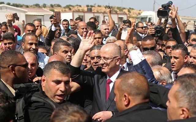 Palestinian Authority Prime Minister Rami Hamdallah (C) is surrounded by security as he waves following his arrival at the Erez border crossing in Beit Hanoun in the northern Gaza Strip on October 2, 2017. ( AFP PHOTO / MAHMUD HAMS)