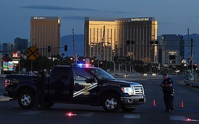 Police form a perimeter around the road leading to the Mandalay Hotel (background) after a gunman killed at least 59 people and wounded more than 500 others when he opened fire on a country music concert in Las Vegas, Nevada on October 2, 2017.  (AFP/ Mark Ralston)