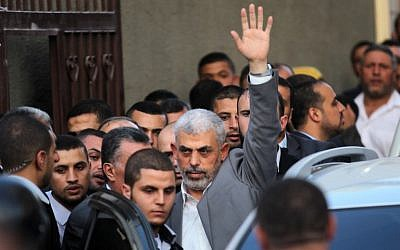The leader of the Hamas terror group in the Gaza Strip, Yahya Sinwar, waves as he arrives for a meeting with the Palestinian Authority's prime minister and other officials in Gaza City on October 2, 2017. (AFP Photo/Said Khatib)