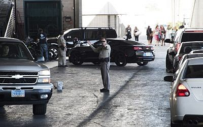 A sheriff's deputy directs cars arriving at the family assistance center at the Las Vegas Convention Center in order to learn more information about their loved ones following a mass shooting, on October 2, 2017. (AFP Photo/Robyn Beck)