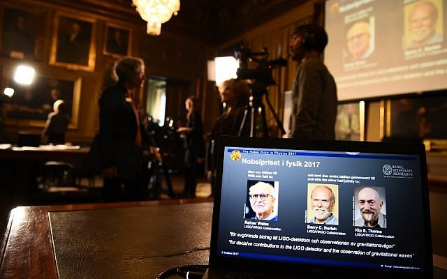 Laureates (L-R) Rainer Weiss, Barry C Barish and Kip Thorne are pictured on a display during the announcement of the 2017 winners of the Nobel Prize in Physics on October 3, 2017, at the Royal Swedish Academy of Sciences in Stockholm. (AFP Photo/Jonathan Nackstrand)