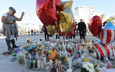 A woman prays at a makeshift memorial on the Las Vegas Strip in Las Vegas, Nevada on October 3, 2017, after a gunman killed 59 people and wounded more than 500 others when he opened fire from a hotel window on a country music festival. (AFP PHOTO / Robyn Beck)