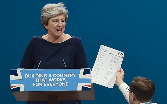 Protester comedian Simon Brodkin (R) gives a piece of paper written as a mock P45 (employee leaving form) to Britain's Prime Minister Theresa May (L) as she delivers a speech on the final day of the Conservative Party annual conference at the Manchester Central Convention Centre in Manchester, England, on October 4, 2017. (AFP Photo/Paul Ellis)
