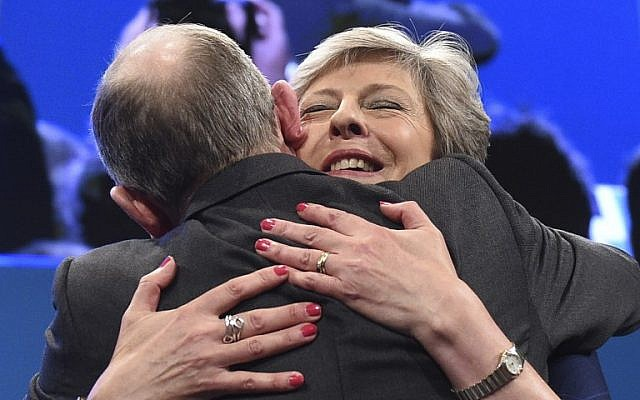 Britain's Prime Minister Theresa May (R) is hugged by her husband Philip May (L) on the stage at the end of her speech on the final day of the Conservative Party annual conference at the Manchester Central Convention Centre in Manchester, northwest England, on October 4, 2017. (AFP PHOTO / Oli SCARFF)