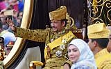Brunei's Sultan Hassanal Bolkiah (L) waves from the royal chariot during a procession to mark his golden jubilee of accession to the throne in Bandar Seri Begawan on October 5, 2017. (Roslan Rahman/AFP)