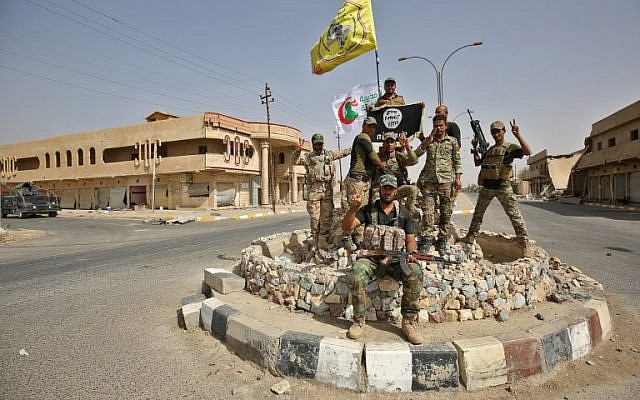 Members of the Iraqi armed forces backed by paramilitary fighters from the Popular Mobilization Forces pose for a photograph in Hawija on October 5, 2017, after retaking the city from the Islamic State terror group. (AFP Photo/Ahmad Al-Rubaye)