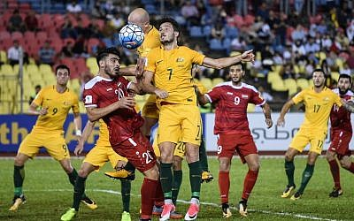 Khaled Almbayed of Syria (2L) and Mathew Leckie of Australia (C) fight for the ball during the 2018 World Cup qualifying soccer match between Syria and Australia at the Hang Jebat Stadium in Malacca on October 5, 2017. (AFP PHOTO/MOHD RASFAN)