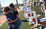 Melissa Gerber, left, and Sandra Serralde, right, comfort each other beside 58 white crosses for the victims of Sunday night's mass shooting on the south end of the Las Vegas Strip, October 6, 2017 in Las Vegas, Nevada. (AFP Photo/Robyn Beck)