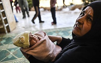 A woman, who along with members of her family was used as human shields by Islamic State (IS) group fighters, holds a new born baby after fleeing from the center of Raqqa, Syria, October 6, 2017. (AFP//BULENT KILIC)