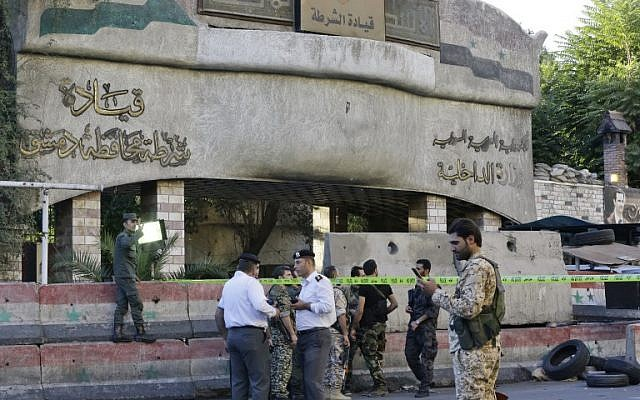 Syrian security forces stand guard outside the main entrance to the police headquarters in Syria's capital Damascus on October 11, 2017, following an attack that targeted the building. (AFP Photo/Louai Beshara)