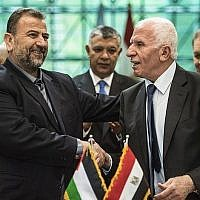 Fatah's Azzam al-Ahmad, right, and Saleh al-Arouri, left, of Hamas shake hands after signing a reconciliation deal in Cairo on October 12, 2017, as the two rival Palestinian movements ended their decade-long split following negotiations overseen by Egypt. (AFP/ KHALED DESOUKI)