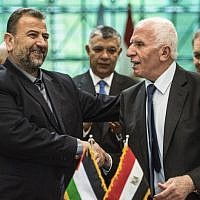Fatah's Azzam al-Ahmad, right, and Saleh al-Arouri, left, of Hamas shake hands after signing a reconciliation deal in Cairo on October 12, 2017, as the two rival Palestinian movements ostensibly ended their decade-long split following negotiations overseen by Egypt. (AFP/Khaled Desouki)