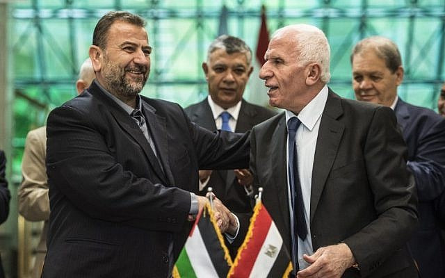 Fatah's Azzam al-Ahmad, right, and Saleh al-Arouri, left, of Hamas shake hands after signing a reconciliation deal in Cairo on October 12, 2017, as the two rival Palestinian movements ended their decade-long split following negotiations overseen by Egypt. (AFP/Khaled Desouki)