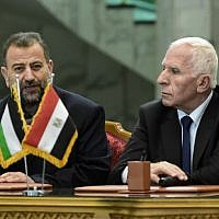 Fatah's Azzam al-Ahmad, right, and Saleh al-Arouri, left, of Hamas talk to journalists after signing a reconciliation deal in Cairo on October 12, 2017, as the two rival Palestinian movements ended their decade-long split following negotiations overseen by Egypt. (AFP/Khaled Desouki)