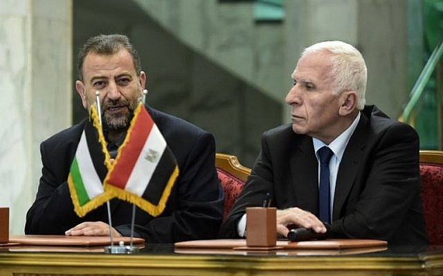Fatah's Azzam al-Ahmad, right, and Saleh al-Arouri, left, of Hamas talk to journalists after signing a reconciliation deal in Cairo on October 12, 2017, as the two rival Palestinian movements ended their decade-long split following negotiations overseen by Egypt. (AFP / KHALED DESOUKI)