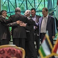 Khaled Fawzi (3rd-L) head of the Egyptian Intelligence services, shares a laugh with Hamas leader Izzat al-Rishq (2nd-L) and Fatah's Azzam al-Ahmad (C) following the signing of a reconciliation deal in Cairo on October 12, 2017. (AFP/Khaled Desouki)