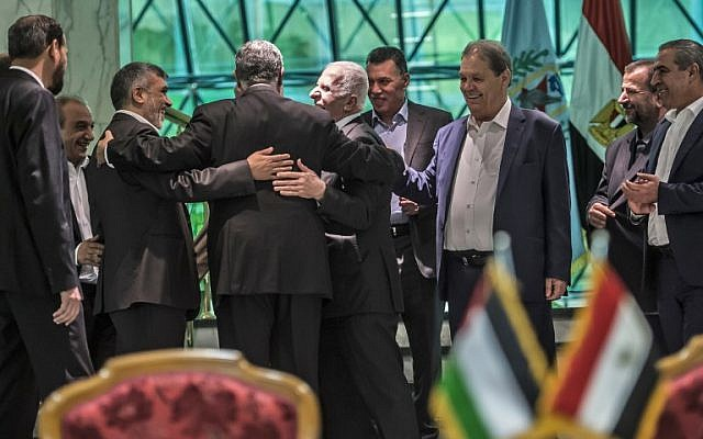 Khaled Fawzi (3rd-L) head of the Egyptian Intelligence services, shares a laugh with Hamas leader Izzat al-Rishq (2nd-L) and Fatah's Azzam al-Ahmad (C) following the signing of a reconciliation deal in Cairo on October 12, 2017. (AFP / KHALED DESOUKI)