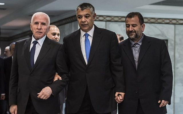 Khaled Fawzi, center, head of the Egyptian Intelligence services, arrives with Fatah's Azzam al-Ahmad, left, and Hamas' Saleh al-Arouri, right, before signing a reconciliation deal in Cairo on October 12, 2017, as the two rival Palestinian movements ended their decade-long split following negotiations overseen by Egypt. (AFP/ KHALED DESOUKI)