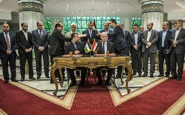 Hamas's new deputy leader Salah al-Arouri (seated, left) and Fatah's Azzam al-Ahmad (seated, right) sign a reconciliation deal in Cairo on October 12, 2017, as the two rival Palestinian movements work to end their decade-long split following negotiations overseen by Egypt. (AFP/Khaled Desouki)