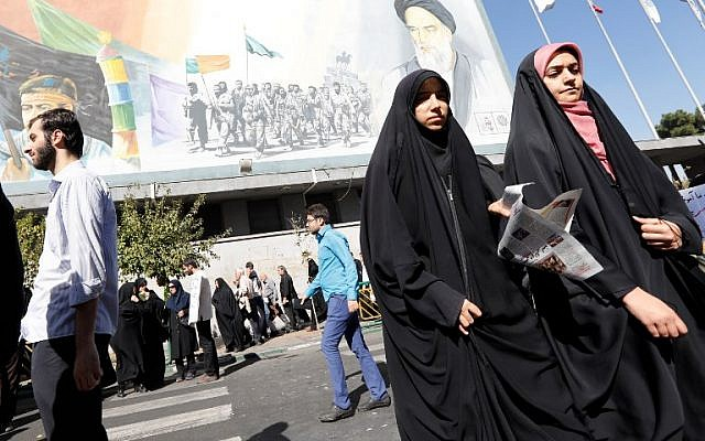 Iranian women walk past a portrait of late Iranian supreme leader Ayatollah Ruhollah Khomeini (top R) following the weekly Friday prayer in Tehran on October 13, 2017. (AFP PHOTO / STR)