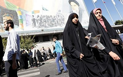 Iranian women walk past a portrait of late Iranian supreme leader Ayatollah Ruhollah Khomeini (top R) following the weekly Friday prayer in Tehran on October 13, 2017. (AFP/STR)