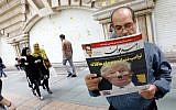 "An Iranian man reads a copy of the daily newspaper 'Omid Javan' bearing a picture of US President Donald Trump with a headline that reads in Persian ""Crazy Trump and logical JCPOA (Joint Comprehensive Plan of Action),"" on October 14, 2017, in front of a kiosk in the capital Tehran. (AFP Photo/STR)"