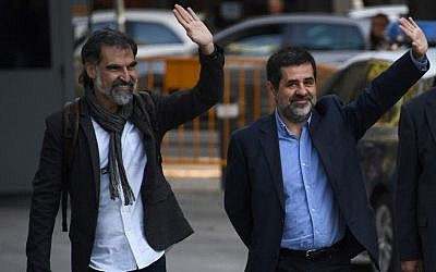 Catalan National Assembly (ANC) president Jordi Sanchez (C), and Pro-independence Catalan Omnium cultural language association president Jordi Cuixart (L), who are under investigation for sedition, wave as they arrive at the High Court in Madrid on October 16, 2017.  / AFP PHOTO/GABRIEL BOUYS)