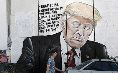 A man walks past a new piece of graffiti depicting US President Donald Trump on the Israeli separation barrier separating the West Bank town of Bethlehem from Jerusalem on October 15, 2017. (AFP Photo/Thomas Coex)