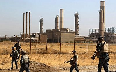 Iraqi forces walk past an oil production plant as they head towards the city of Kirkuk during an operation against Kurdish fighters on October 16, 2017. (AFP Photo/ Ahmad Al-Rubaye)
