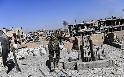 Members of the Syrian Democratic Forces, backed by US special forces, walk on a building near Raqqa's central hospital as they clear the last positions on the frontline in the Islamic State group jihadists crumbling stronghold, October 16, 2017. (AFP/BULENT KILIC)