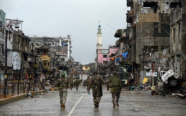 "Filipino soldiers walk past destroyed in Marawi after President Rodrigo Duterte declared the city ""liberated"" on October 17, 2017. (AFP Photo/Ted Aljibe)"