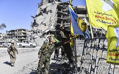 Members of the Syrian Democratic Forces (SDF), backed by US special forces, place their flags at the iconic Al-Naim square in Raqa on October 17, 2017. (Bulent Kilic/AFP)
