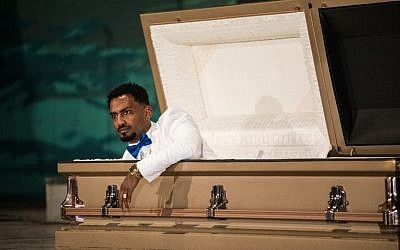 "Ethiopian film director Zekarias Mesfin surprises the audience by appearing from inside a coffin on the stage of the National Theater of Ethiopia, during the premiere of his film ""Ewir Amora Kelabi"" in Addis Ababa, October 16, 2017. (AFP/Zacharias ABUBEKER)"