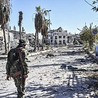 Illustrative: A member of the Syrian Democratic Forces (SDF) walks through a heavily damaged a street leading to an Armenian church in Raqqa, Syria, October 18, 2017. (Bulent Kilic/AFP)