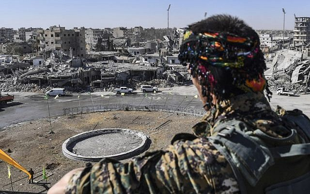 A member of the Syrian Democratic Forces (SDF) stands at a position overlooking the iconic Al-Naim square in Raqa on October 18, 2017. (AFP/Bulent Kilic)