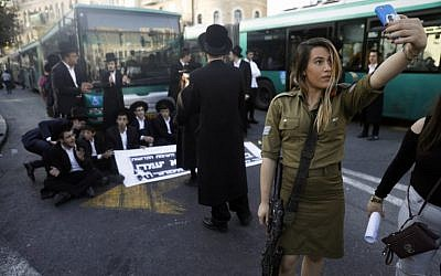 A female IDF soldier uses her cell phone to take a selfie as ultra-Orthodox Jews take part in a demonstration in Jerusalem against the conscription of members of the ultra-Orthodox community to the IDF on October 19, 2017. (AFP Photo/Menahem Kahana)