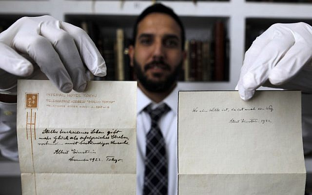 A picture taken on October 19, 2017, shows Gal Wiener, owner and manager of the Winner's auction house in Jerusalem, displaying two notes written by Albert Einstein, in 1922, on hotel stationary from the Imperial Hotel in Tokyo Japan. A note that Albert Einstein gave to a courier in Tokyo, briefly describing his theory on happy living, has surfaced after 95 years and is up for auction in Jerusalem. (AFP PHOTO / MENAHEM KAHANA)