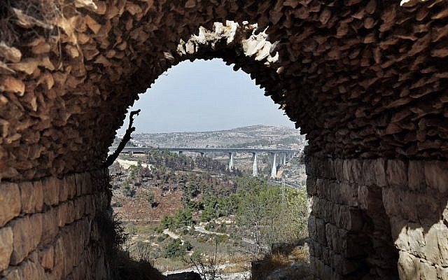 A picture taken from inside an old house in Palestinian village of Lifta which was abandoned during fighting in the 1948 Arab-Israeli war, shows the bridge for a new train line on the outskirts of Jerusalem, on October 20, 2017. (AFP PHOTO / THOMAS COEX)