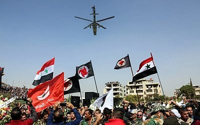 Syrians wave their national flags and those of the Syrian Social Nationalist Party in a stadium as a Russian-made Mil Mi-24 helicopter gunship hovers above during the funeral for Brigadier General Issam Zahreddine, in the southern city of Suwaida on October 20, 2017. (AFP/Stringer)