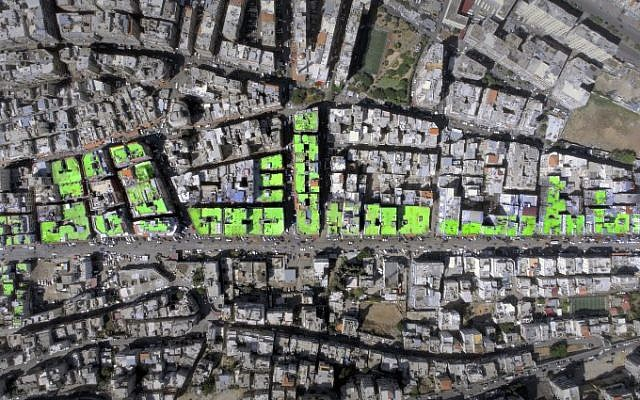 """An aerial view of the word """"Peace"""" in Arabic painted on the roofs of 85 buildings in Tripoli's Syria street which separates the Sunni neighborhood of Bab al-Tabbaneh from the Alawite neighborhood of Jabal Mohsen. The project has been three years in the making, with the artists, 34-year-old twins Mohamed and Omar Kabbani, researching and rejecting multiple locations in their native Lebanon before settling on Tripoli. (AFP PHOTO / ASHEKMAN / Handout)"""