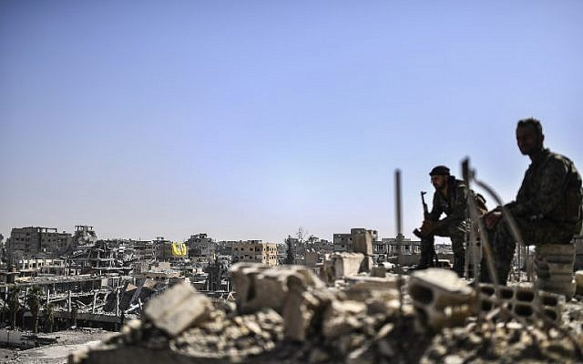 Fighters from the Syrian Democratic Forces stand guard on a rooftop in Raqqa on October 20, 2017, after retaking the city from the Islamic State. (AFP Photo/Bulent Kilic)
