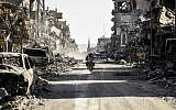 A Syrian youth uses his cell phone to film the destroyed vehicles and heavily damaged buildings down a street in Raqqa on October 20, 2017. (AFP/BULENT KILIC)